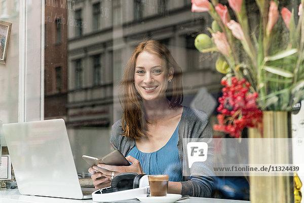 Porträt einer lächelnden Frau mit Smartphone und Laptop im Coffee-Shop