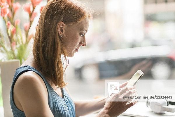 Frau in einem Coffee-Shop mit Blick auf Smartphone