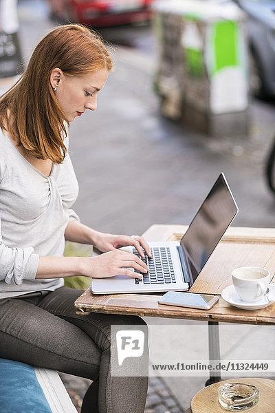 Redheaded woman using laptop at sidewalk cafe