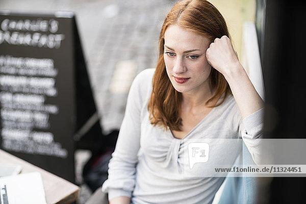 Nachdenkliche Frau im Straßencafé
