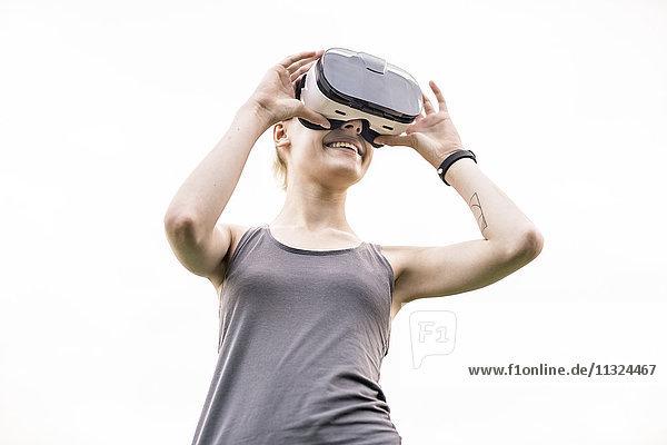 Lächelnde junge Frau mit Virtual Reality Brille im Freien