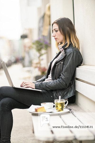 Junge Frau sitzend auf der Außenbank mit Laptop