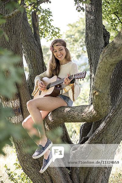Glückliche junge Frau spielt Gitarre im Baum