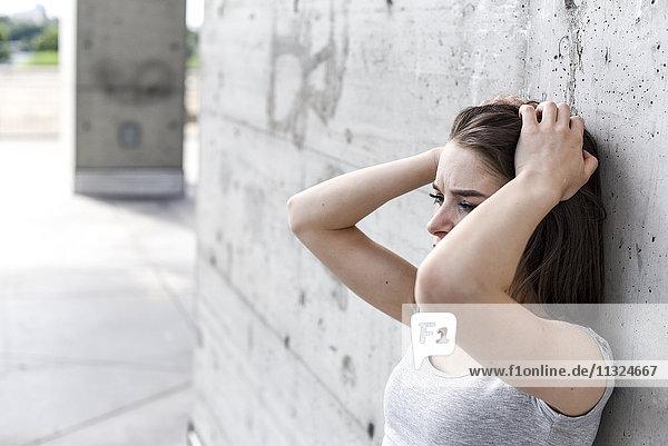Verzweifelte junge Frau mit Händen auf dem Kopf