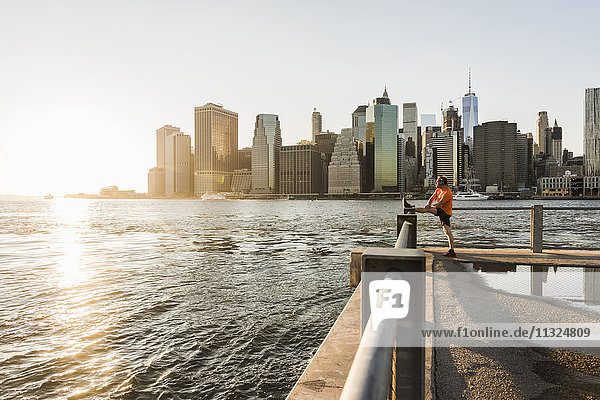 USA  Brooklyn  Mann beim Stretching vor der Skyline von Manhattan am Abend