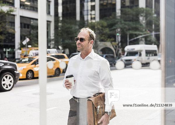 USA  New York City  selbstbewusster Geschäftsmann in Manhattan mit Kaffee zum Mitnehmen