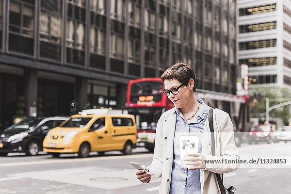 USA  New York City  Frau in Manhattan sucht Handy