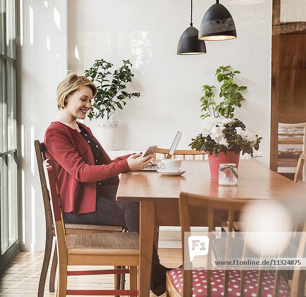 Lächelnde junge Frau mit Handy und Laptop im Cafe