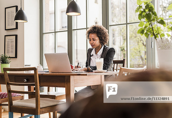 Junge Frau  die in einem Café arbeitet.