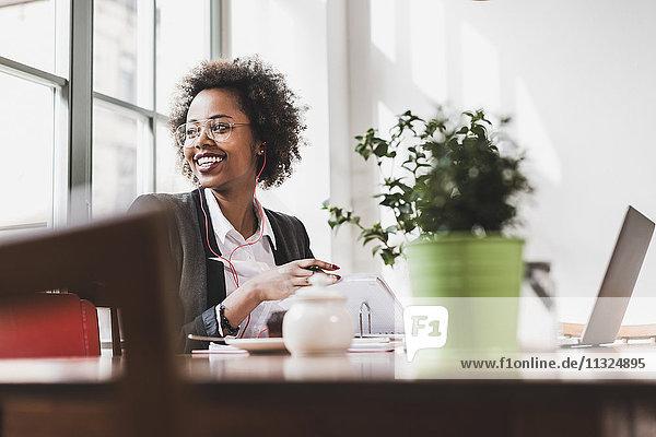 Lächelnde junge Frau bei der Arbeit in einem Café
