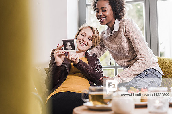 Pregnant young woman showing ultrasound scan to friend in a cafe