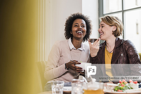 Two happy young women using cell phone in a cafe
