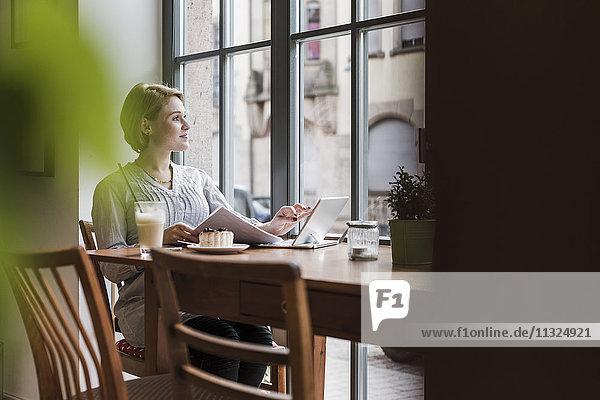 Junge Frau mit Tablette in einem Café mit Blick aus dem Fenster
