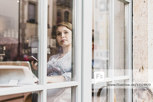 Junge Frau mit Tablette und Handy in einem Café mit Blick aus dem Fenster