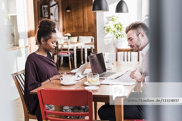 Junger Mann und Frau mit Laptop und Tablett in einem Cafe