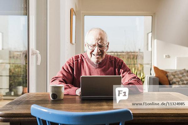 Senior man sitting at home  using laptop
