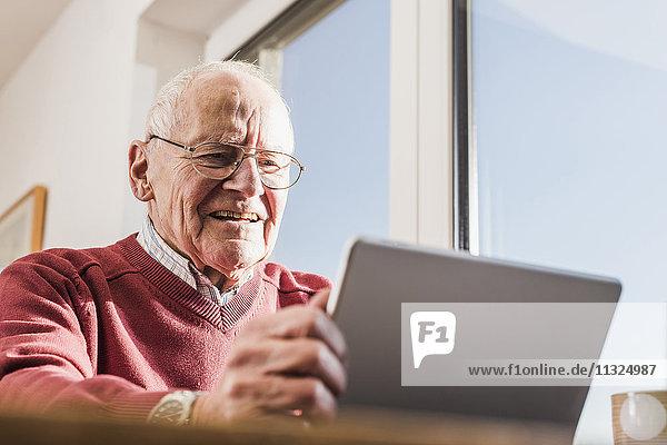 Senior Mann sitzt zu Hause  mit Laptop