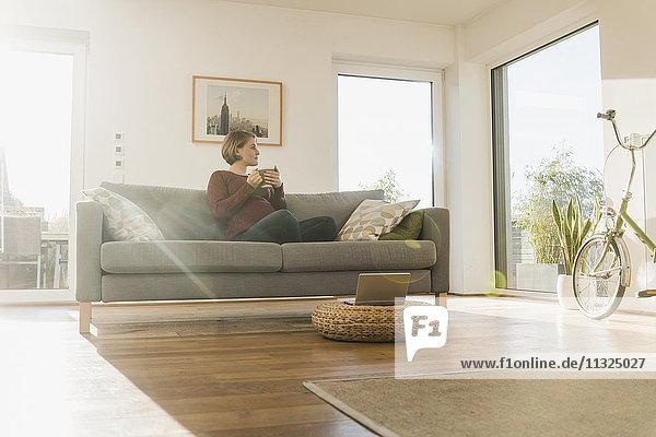 Schwangere Frau auf der Couch mit Henkelbecher