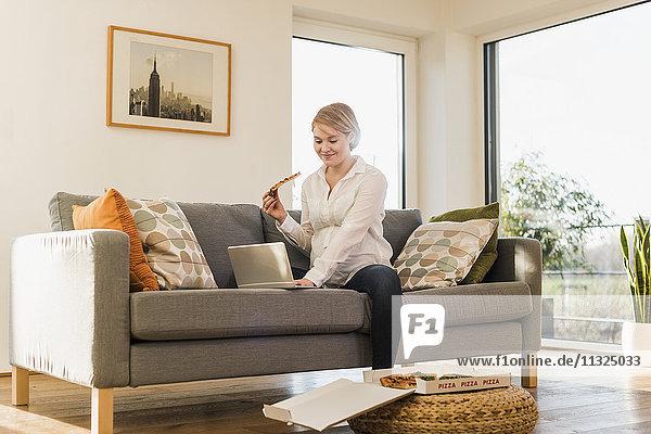 Lächelnde schwangere Frau auf der Couch  die ein Stück Pizza mit dem Laptop hält.