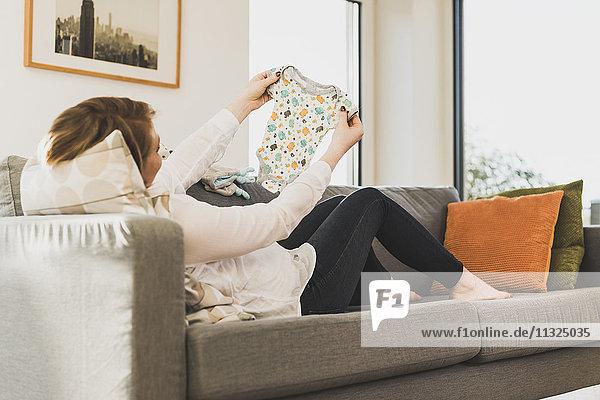 Schwangere Frau auf der Couch mit Babykleidung