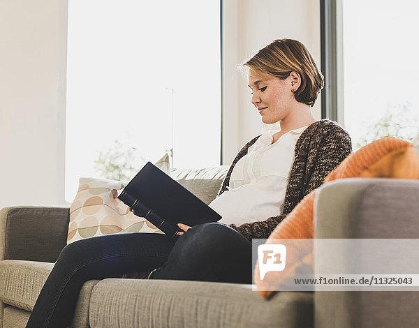 Schwangere Frau auf der Couch Lesebuch