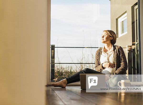 Schwangere Frau sitzt auf dem Boden mit Laptop und genießt die Sonne.
