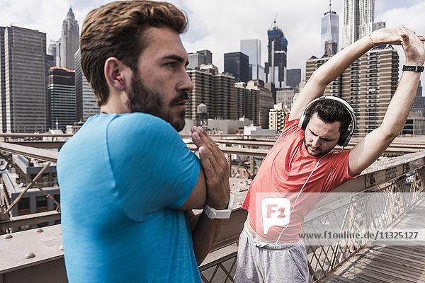 USA  New York City  two athletes stretching on Brooklyn Brige