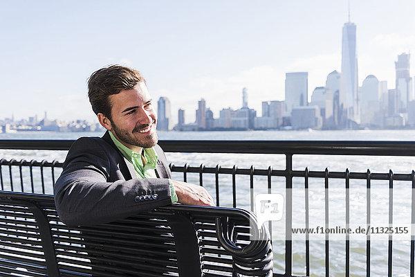 USA  lächelnder Mann sitzt auf der Bank am Ufer von New Jersey mit Blick auf Manhattan USA, lächelnder Mann sitzt auf der Bank am Ufer von New Jersey mit Blick auf Manhattan