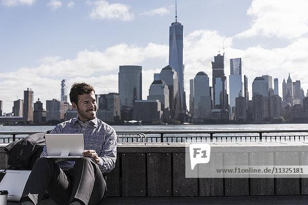 USA  Mann mit Tablette am New Jersey Waterfront mit Blick auf Manhattan USA, Mann mit Tablette am New Jersey Waterfront mit Blick auf Manhattan