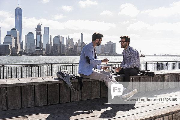 USA  zwei Geschäftsleute  die an der Waterfront von New Jersey mit Blick auf Manhattan arbeiten.