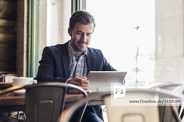Geschäftsmann mit Tablette in einem Café Geschäftsmann mit Tablette in einem Café