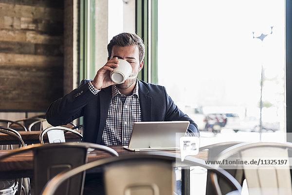 Geschäftsmann  der Kaffee trinkt und Tabletten in einem Café benutzt. Geschäftsmann, der Kaffee trinkt und Tabletten in einem Café benutzt.