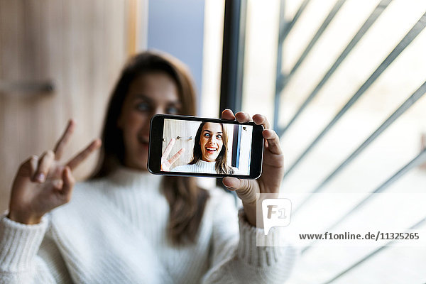 Playful young woman taking a selfie with cell phone