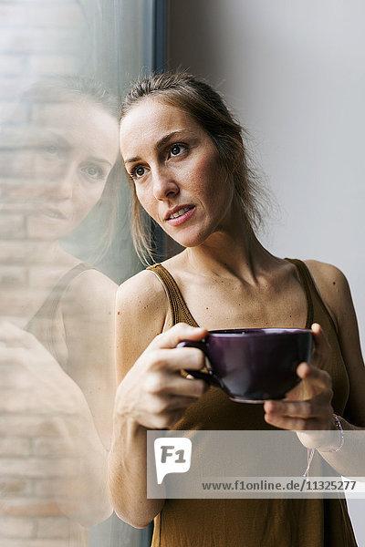 Frau schaut aus dem Fenster und trinkt Kaffee.
