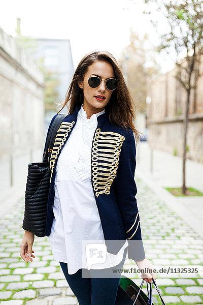 Modische junge Frau mit Sonnenbrille und Einkaufstaschen
