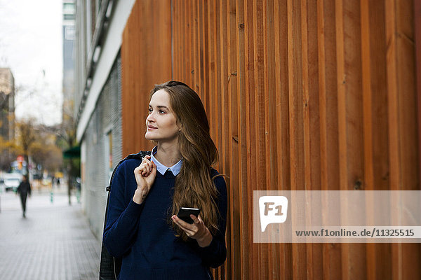 Relaxed young woman with smartphone