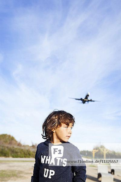 Kleiner Junge schaut über die Schulter zum Flugzeug im Hintergrund Kleiner Junge schaut über die Schulter zum Flugzeug im Hintergrund