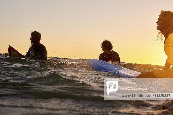 Drei Surfer im Meer bei Sonnenuntergang