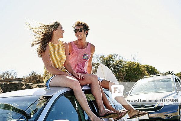 Lächelndes junges Paar auf dem Autodach sitzend