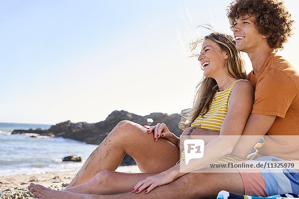 Glückliches Paar am Strand sitzend