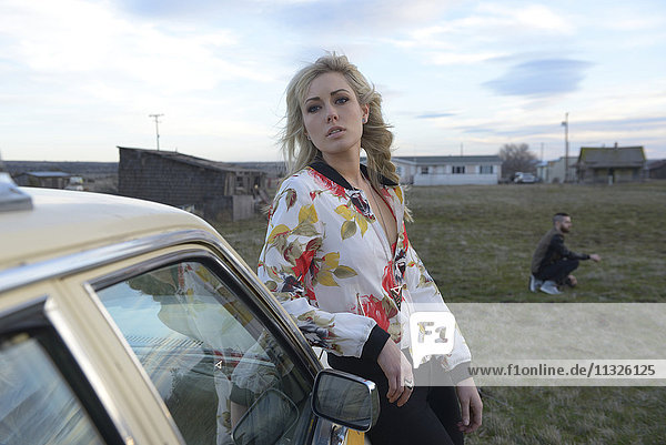 american woman standing at the car