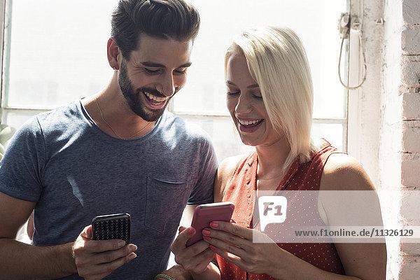 Glückliches junges Paar mit Handys am Fenster