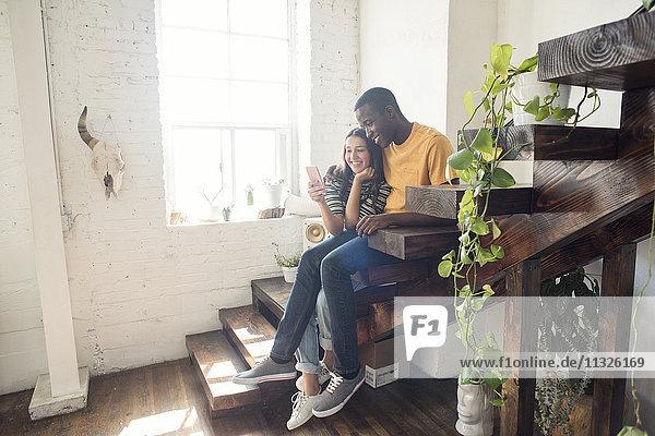 Lächelndes junges Paar sitzt auf einer Treppe in einem Loft und teilt sich ein Handy.