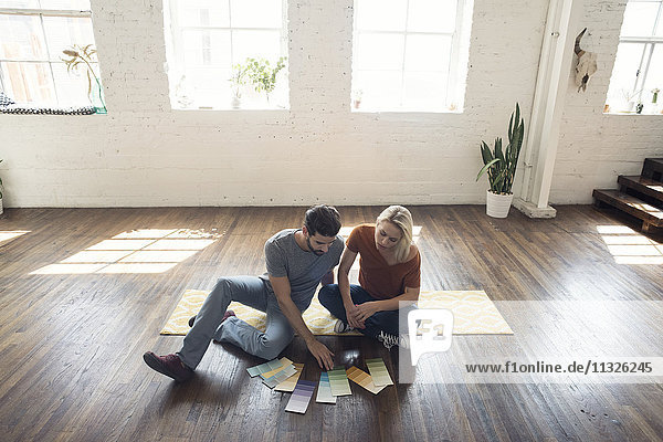 Junges Paar sitzt auf einem Teppich in einem Loft und sieht sich Farbmuster an.