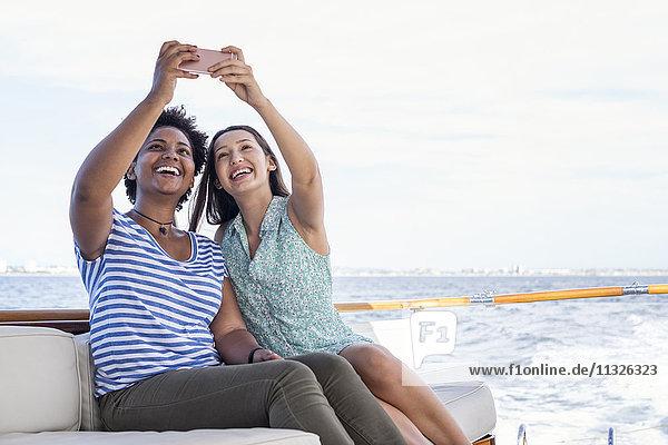 Zwei glückliche junge Frauen auf einer Bootsfahrt mit einem Selfie