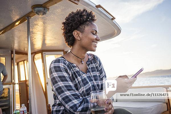 Lächelnde junge Frau auf einem Boot beim Handychecken