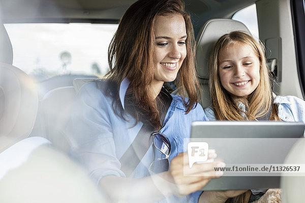 Mutter und Tochter sitzen im Auto und sehen sich das digitale Tablett an.