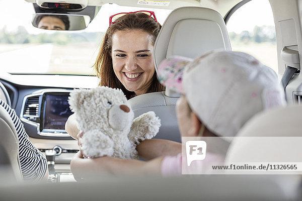 Mutter und Tochter auf Roadtrip sitzend im Auto mit Teddybär