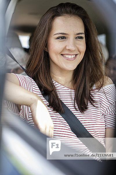 Frau im Auto sitzend mit angeschnallten Sicherheitsgurten