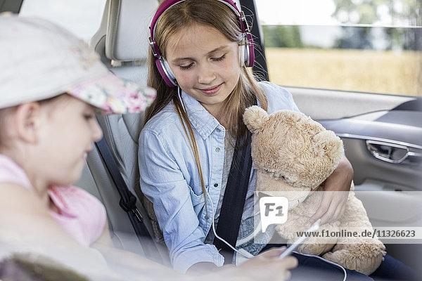Mädchen im Auto sitzend mit Teddybär